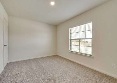 Sabine bedroom finished with lightly colored carpet, large street facing window with blinds, and recessed light
