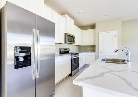A kitchen in the St. Johns floor plan with tile flooring, stainless steelappliances and a pantry.