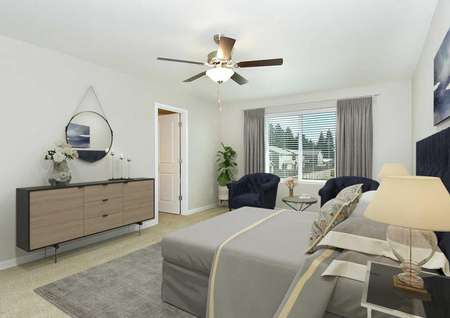 Northwest staged master bedroom with mid-century modern furnishings, carpet, ceiling fan, upstairs window view and door to bathroom.