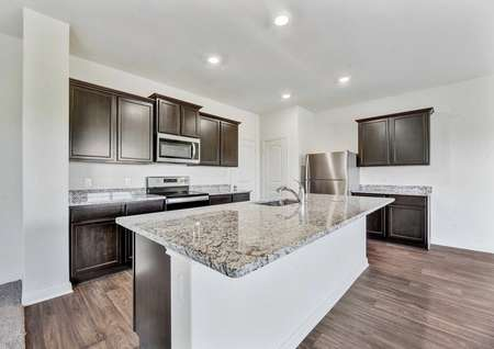 Rio kitchen with recessed lights, large granite kitchen island, and brown custom cabinets