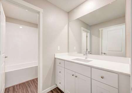 A bathroom in the Empire floor plan with marble countertops, white cabinets and a door leading to the tub and toilet.