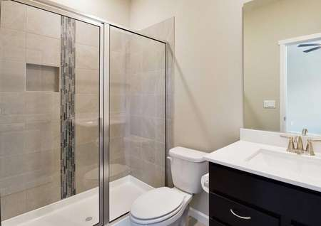The Northwest Aspen master bath is shown with glass walk in shower and a white quartz sink countertop.