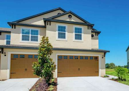 The exterior view of the Tuscany floor plan that has an orange garage with white trim around it and the home is painted tan.
