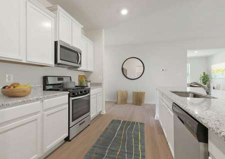 Staged kitchen with white cabinets, plank flooring, stainless range with overhead microwave, granite counters, runner rug, into foyer with circle mirror, stools, view of dining room with artwork and tall plant in corner.