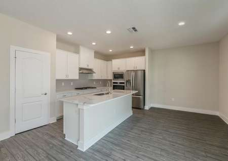 Open, chef-ready kitchen with quartz countertops, stainless steel appliances, recessed lighting and luxury vinyl plank flooring.