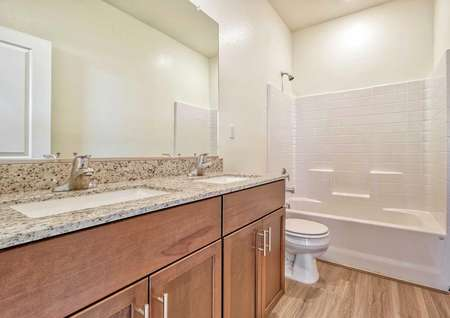 A bathroom with two sinks, granite countertops, browns cabinets and vinyl wood floors in the Sunflower floor plan.