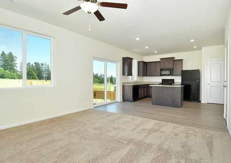 Cypress great room with ceiling fan, recessed lights, and wood cabinetry in the kitchen