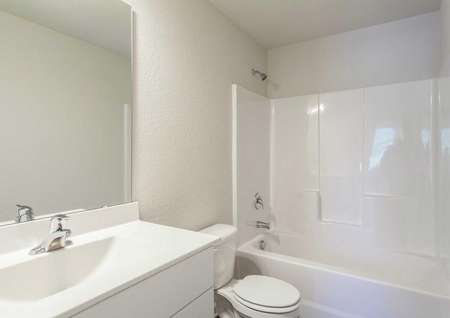 Alexander bathroom with shower/bath combo, toilet, and white vanity