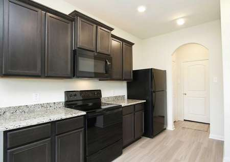Partial image of the Mesquite plan's kitchen with granite countertops, black appliances, dark brown cabinetry with crown molding and wood-style vinyl flooring