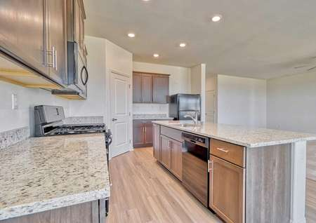 The Sunflower floor plan's kitchen with black appliances, recessed lighting and brown cabinet hardware.