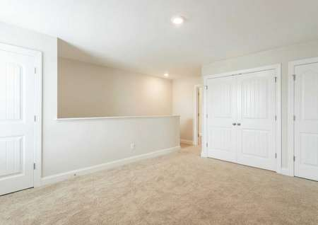 Avery loft with white French doors, light brown carpeting, and stairs to lower level