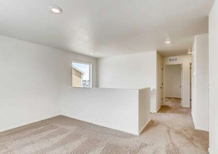 Yale loft with large window, ceiling lights, and tan carpeted floor