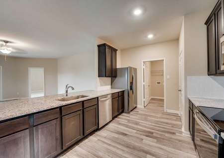 Houghton floor plan's kitchen featuring granite countertops, new appliances and leads to the laundry room.