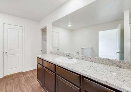 The Rio plan's master bathroom's granite countertops and dark brown cabinetry surrounded by wood-style vinyl flooring