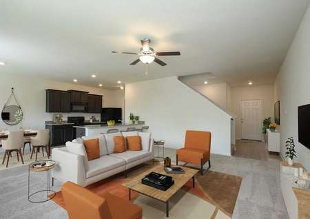 Open and spacious living room, breakfast area and kitchen decorated with beige and orange, ceiling fan and recessed lighting.