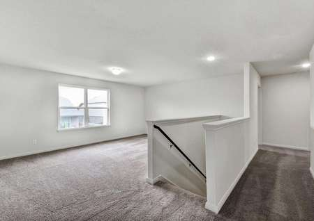 Victoria loft with recessed lights, large white framed window, and soft brown carpeting