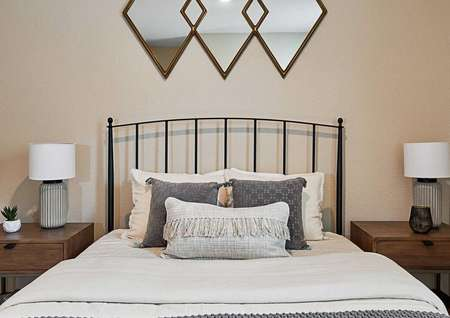 Staged bedroom with two night stands and decorative mirror above the bed.