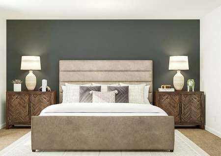 Rendering of owners bedroom with large   bed, dark gray accent wall and dual side tables.