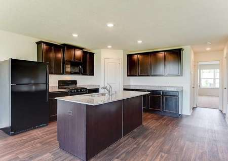 Hennepin kitchen with brown cabinets, recessed lights, and black appliances