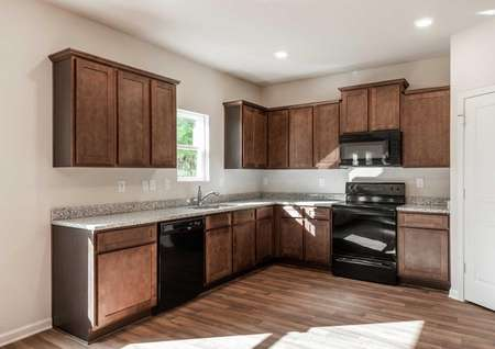 Hartwell kitchen finished with brown cabinets, granite countertops, and recessed lights
