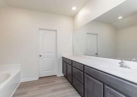 The master bath Osagewith dark brown cabinets, cultured marble countertops, vinyl flooringand garden tub. A door is visible