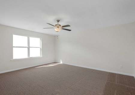 The master bedroom of the Claireborne model home with tan carpet, white baseboards, ceiling fan and large window on the left wall
