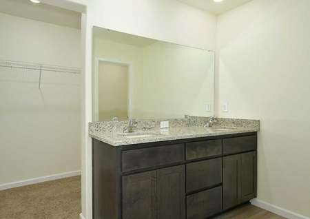 The Northwest Oak master bathroom showing a dual granite sink and doorway to the walk in closet.