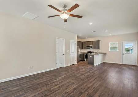 This home has an open layout with dark wood-like flooring and tan walls with white trim.