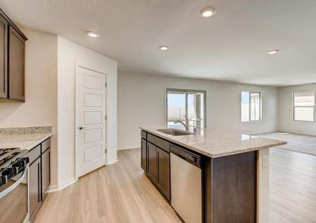 A chef-ready kitchen with a large walk-in pantry, granite countertops and a view of the family room.