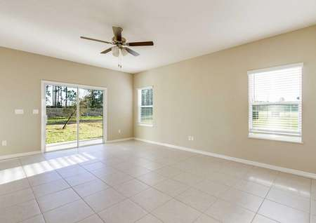 The large living area in the Mykka floor plan with tile flooring, two windows, a ceiling fan and a sliding glass door.