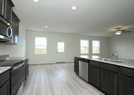 Photo of kitchen with dark brown cabinets, granite counters, light gray plank flooring looking into adjacent dining and living rooms.