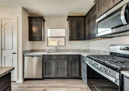 The kitchen features stainless steel appliances with a gas stove.
