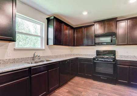 Chippewa finished kitchen with brown cabinets, granite counters, and modern black appliances