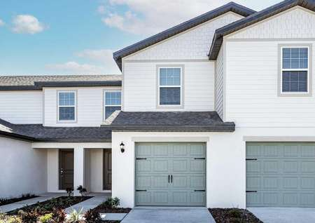 Sizable, new-construction home with front yard landscaping and a one-car garage.