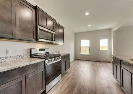 The kitchen is open to the dining area and features stainless steel appliances and a gas stove.