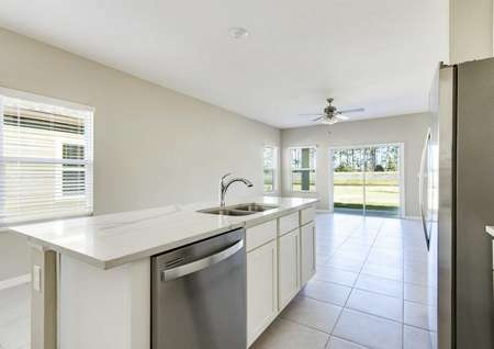 The kitchen and living room area of the Alafia floor plan has tile flooring, white baseboards and tan walls.