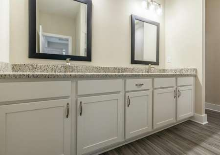 Double sinks with granite countertops and white cabinets with plenty of storage space.