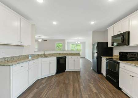 Burton kitchen with new black appliances, dark wood looking flooring, and white cabinetry with granite tops