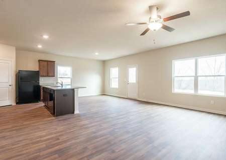 Camden great room with hardwood floors, white trim walls with white door, and overhead ceiling fan