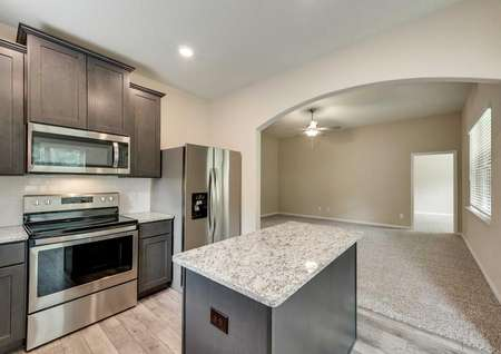 Erie kitchen with dark brown cabinetry, modern appliances, and granite countertops