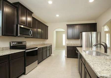 Spacious kitchen with close up of granite counters, antique bronze faucet, espresso cabinets,tile floor, stainless appliances, recessed lighting looks into formal dining and foyer.