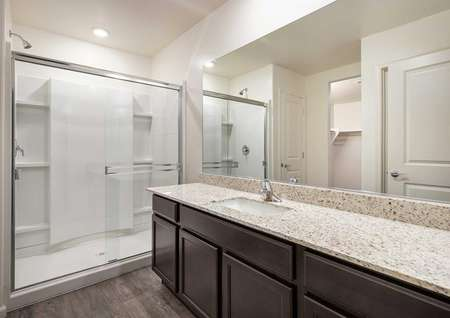 The Roosevelt master bath room shown with granite sink countertops and a glass walk in shower.