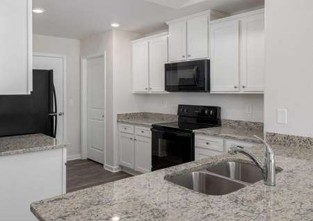 Alamance kitchen with granite counters, white cabinets, and black appliances