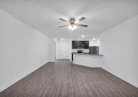 A spacious family room with luxury vinyl plank flooring that leads to a chef-ready kitchen.