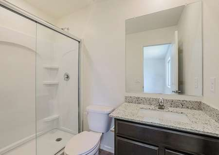 Master bathroom with granite countertops and a white-tiled shower.