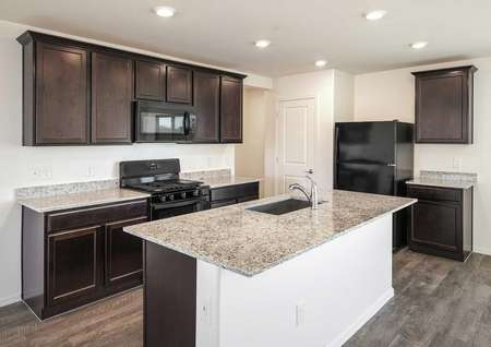 The Alamo floor plan kitchen shown with dark brown cabinets and black appliances.