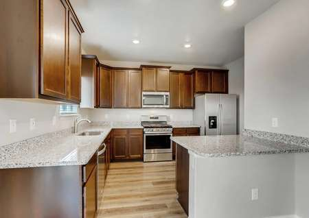 Mesa Verde finished kitchen with brown cabinets, wood floors, and granite countertops