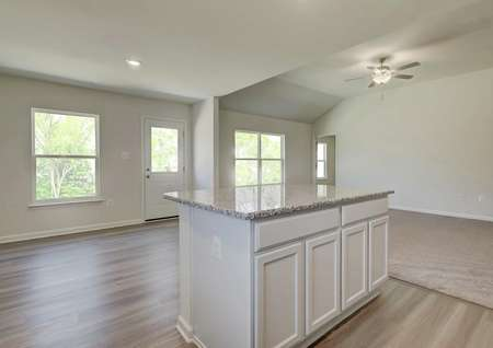 Open and spacious entertaining area with kitchen, dining, living rooms, windows, fan, plank flooring.