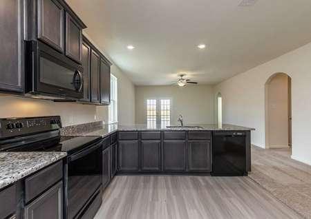 Maple kitchen completed with granite countertops, custom wood cabinetry, and black appliances