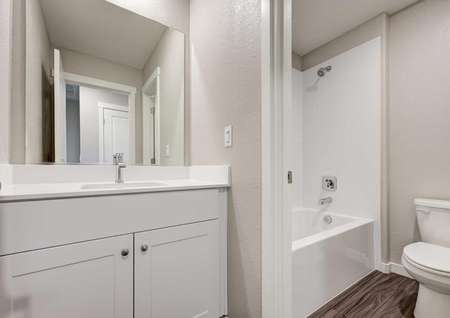 A bathroom with asink, white cabinets, a bath/shower combo and wood-like flooring in the Loomis floor plan.